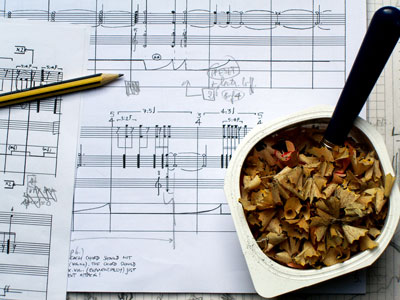 Scene of breakfast of music scores and pencil.